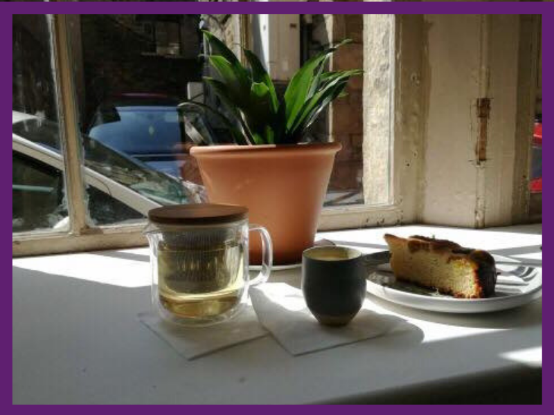 photo of a cup of tea and slice of cake on a windowsill in a cafe