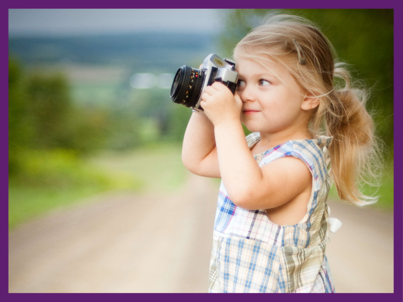 photo of little girl holding up a camera to take a photo