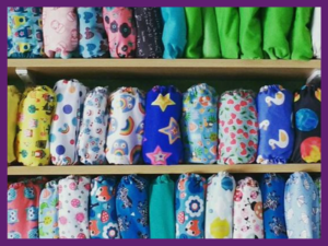 image of 3 shelves of bright and colourful resuable nappies